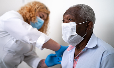 A health care worker administers a COVID-19 vaccination to an older Black man who is wearing a mask.